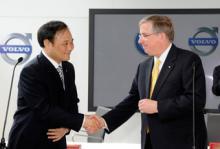 Geelys ordförande Li Shufu skakar hand med Fords finanschef Lewis Booth.
