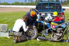 """Speedway-hojar är okomplicerade, """"som en trampcykel  med motor"""" säger Varg-Olle. Motorn är en 500-kubiks fyrtaktare som drivs med metanol. En växel och inga bromsar. Här har Jonas Jarlmark och Gunnar Lund tagit sig för att byta bakdrev för att få lägre utväxling, vilket passar bättre på den ganska tajta banan i Örebro."""