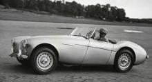 """""""Dir. Raymond Sjökvist demonstrerade på Skarpnäck den nyaste fashionabla sportvagnen Austin-Healey 100, som gör sina modiga 180 km i timmen. Här ses han rusa fram i hög hastighet med sitt stilrena fartvidunder."""" Bilden är tagen 1 september 1953 och Sjökvist var mannen bakom Räddningskåren."""