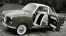 Mysputtrig deluxe-coupé i fickformat: Goggomobil på 13,6, 15 eller 18 hk. Bänk bak, lyxratt i vitt, fejkade ekerkapslar och fejkad grill i nosen.