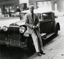 Prins Axel av Danmark lutar sig mot sin luxuösa Lancia Dilambda vid Grand Hotel Haglund på Södra Hamngatan i Göteborg. Bilden är tagen i juni 1935.