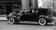 I trafikvimlet på 5th Avenue i New York glider en specialkarosserad Lincoln förbi. Här sitter chauffören exponerad för regn och rusk medan herrskapet diskret döljer sig där bak.