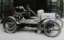 Rovers första lilla bil kallades 8HP och presenterades 1904. Skylten på muren bakom bilen berättar att firman heter The Rover Bicycle Co. Ltd.