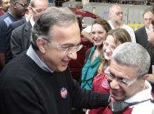 """Sergio Marchionne, vd för Chrysler och Fiat, besökte bilfabriken i Sterling Heights, Michigan, med en knapp med texten """"Paid"""" på bröstet."""