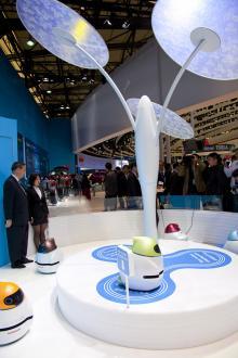 """Hos Nissan pilar små elektriska robotar runt ett """"träd"""" som består av solceller, vilka producerar ström.  Under trädet finns parkeringsplatser där robotarna kan ladda sina batterier. Runt år 2030 kan laddningsträden vara tillräckligt effektiva för att klara elbilar."""