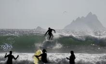 Surfare och sjöfåglar trivs på stranden i St Finans Bay, med Skellig Islands i bakgrunden.