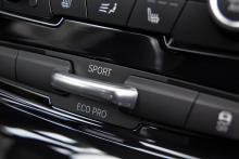 Det lilla handtaget i mittkonsolen vippas upp eller ner mellan körlägena Normal, Sport och ECO-pro.