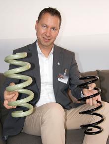 Mathias Mader visar den nya glasfiberfjädern och den äldre, tyngre typen av stål.