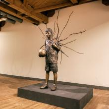 """Skulpturen """"Jag kan vara med i vilket lag som helst"""" av Knutte Wester visas på konsthallen Havremagasinet. Byggnaden fungerade tidigare som fodermagasin för försvarsmaktens hästar, berättar koordinatorn."""