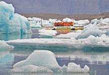På en amfibiebåt kan turisterna kryssa mellan isbergen på Jökulsárlón.