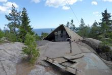 Ett kanontorn sticker upp ur marken ovanför försvarsanläggningen Hemsö fästning som dolts inne i berget.
