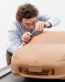 """Vi Bilägares reporter provar modellöryrket. Leran läggs i ett par centimeter tjockt lager över ett """"chassi"""" av metall och trä. Leran kan stå i flera år utan att torka. Lerkostnaden för en modell är omkring 2000 pund. Modellerna sparas så länge det är ett pågående projekt. All lera återanvänds."""