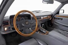 I tidiga XJ-S fanns inga träpaneler. Först 1981 levererades bilar med inlägg av alm, senare (som här) av valnöt. Kupén är kompakt och ytterst engelsk i stilen, med elegant, kromad växelväljare och, förstås, dubbla askfat.