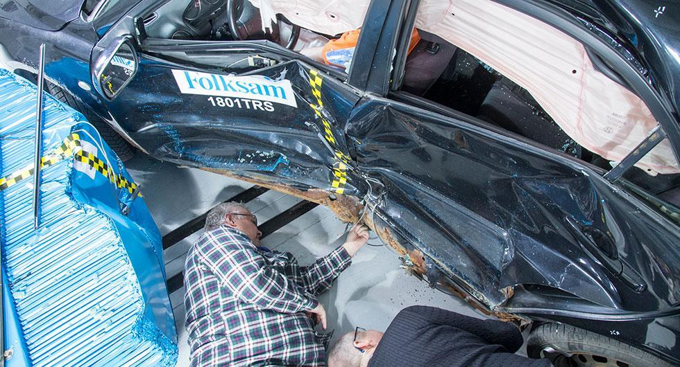 Vi Bilägares rostskyddsexpert Thomas Widström undersöker tillsammans med Folksams Anders Kullgren en av de rostiga Mazdabilarna efter krocktestet.