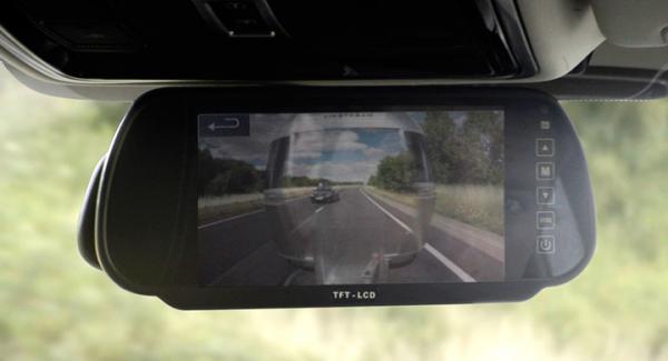 Släpet blir genomskinligt i bilens backspegel.