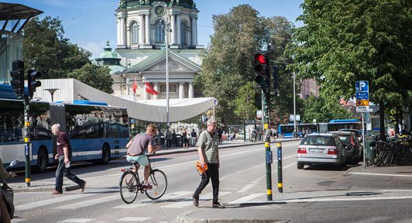 Cyklist kör mot rött och sicksackar mellan gående.